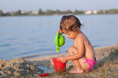 Girl playing with watering can and bucket at beach Royalty Free Stock Image