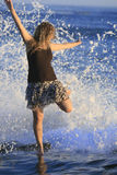 Girl playing in waves Royalty Free Stock Photos