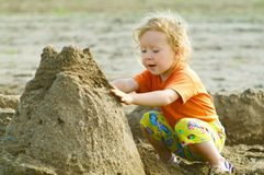 Girl playing with wet sand Stock Photos