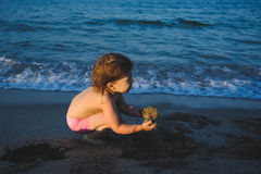 Girl Playing with Wet Sand Stock Images