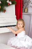 Girl playing on white piano. Girl in concert dress playing on white piano Royalty Free Stock Images