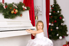 Girl playing on white piano. Girl in concert dress playing on white piano Royalty Free Stock Image