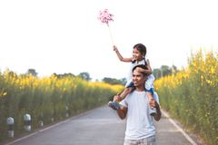 Girl playing with wind turbine and riding on father`s shoulders. Cute asian little girl playing with wind turbine and riding on father`s shoulders in the flower Royalty Free Stock Image