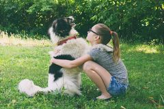 Free Girl Playing With Dog On Grass. Teenager Hugging Carpathian Shepherd Dog In The Summer Park. Friendship Concept Of Man And Animal Royalty Free Stock Images - 151008059