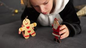 Girl playing with wooden dolls decorations for the Christmas tree. Christmas Eve. Baby dressed in fleece pajamas stock footage