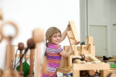 Girl playing in wooden puzzles. Cute schoolgirl playing in wooden puzzles stock photography