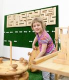 Girl playing with wooden puzzles. Girl of 5 years collecting wooden puzzle in playroom stock photography