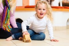 Girl playing wooden toy car Stock Photography