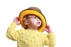 Girl playing with yellow hat Royalty Free Stock Photos