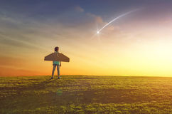 Girl plays astronaut. Little girl plays astronaut. Child on the background of sunset sky. Kid is looking at falling star and dreaming of becoming a spaceman royalty free stock photo