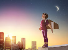 Girl plays astronaut. Little child girl plays astronaut. Child on the background of sunset sky. Child in an astronaut costume plays and dreams of becoming a royalty free stock photography