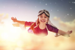 Girl plays astronaut. Little child girl plays astronaut. Child on the background of sunset sky. Child in an astronaut costume plays and dreams of becoming a stock photo