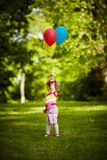 Girl plays with balloons in park Stock Photography
