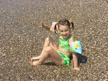A girl plays on the beach at water Stock Images