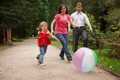 Girl plays with big ball in park with parents Stock Photos
