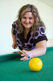 The girl plays billiards. Attractive brunette playing pool with smile on her face Stock Photos