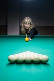 The girl plays billiards. The girl begins a game of billiard Stock Image