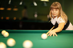 Girl plays billiards Royalty Free Stock Photography