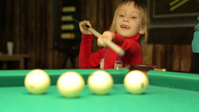 Girl plays billiards. Little girl plays billiards, she does not know how to play stock video footage