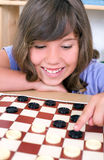Girl plays checkers royalty free stock photo