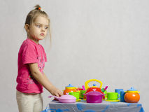 The girl in surprise looking at the dishes playing child kitchen utensils Royalty Free Stock Photos