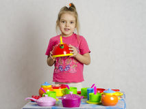 The girl keeps in the hands of the maker playing child kitchen utensils Royalty Free Stock Photography
