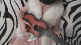 A girl plays in a child`s guitar. The view from the top stock footage