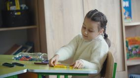 Girl plays with the designer. Girl plays with a designer sitting at her desk stock footage