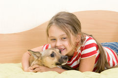 Girl plays a dog. Lying on a bed of yellow color Stock Images