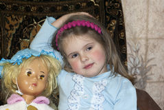 The girl plays a doll. The girl plays a favourite toy a doll Royalty Free Stock Photography