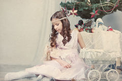 Girl plays with doll around Christmas tree Royalty Free Stock Photography