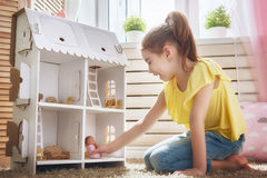 Girl plays with doll house stock image