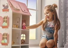 Girl plays with doll house Stock Photos