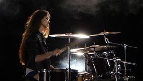 Girl plays the drum she likes to pound on pancakes. Black smoke background. Side view. Girl plays fast music on the drum, her long hair fluttering in the wind stock video footage