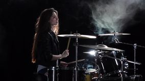 Girl plays the drum she likes to pound on pancakes. Black smoke background. Side view. Slow motion. Girl plays fast music on the drum, her long hair fluttering stock video