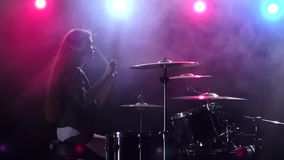 Girl plays the drums and smiles. Black smoke background. Red blue light from behind. Side view. Slow motion. Girl plays vigorous music on the drums, her hair stock footage
