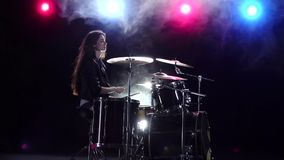 Girl plays the drums and smiles. Black smoke background. Red blue light from behind. Side view. Slow motion. Girl plays vigorous music on the drums, her hair stock video