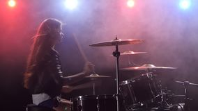 Girl plays the drums and smiles. Black smoke background. Red blue light from behind. Side view. Girl plays vigorous music on the drums, her hair develops in the stock video