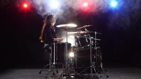 Girl plays the drums and smiles. Black smoke background. Red blue light from behind. Side view. Girl plays vigorous music on the drums, her hair develops in the stock footage