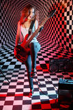 Girl plays electric guitar and sings in studio Stock Images