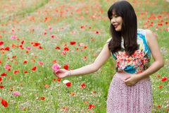 Girl plays with a flower in poppy field royalty free stock photography