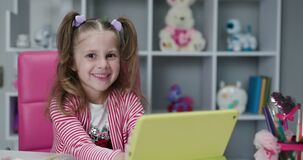 Kid girl using digital tablet technology device and looks at the camera. Small child hold tablet computer play game at