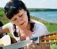 Girl plays a guitar Stock Images