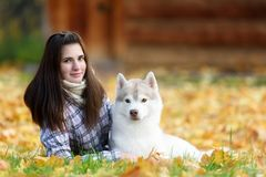 Girl plays with her dog in fallen autumn leaves. Girl plays with her husky dog in fallen autumn leaves royalty free stock images