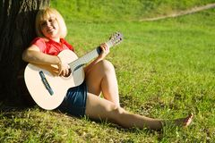 Girl plays her guitar Stock Photography