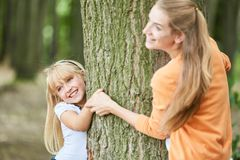 Girl plays hide with the mother stock photography