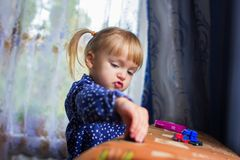 The girl plays house toys. The little girl plays house machines on a sofa Royalty Free Stock Photography
