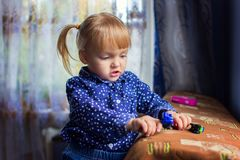 The girl plays house toys. The little girl plays house machines on a sofa Stock Photo