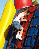 Girl Plays Inflatable Bouncy. A Cute Little Girl Climbing and Playing On An Inflatable Carnival Bouncy Royalty Free Stock Image