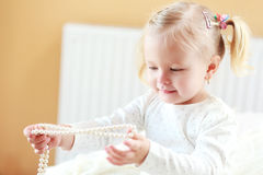 Girl plays with jewelry Stock Photos